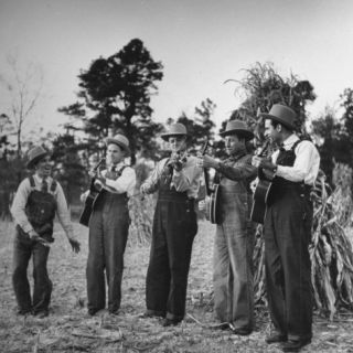 Five Male Musicians Dressed in Hats and Bib Overalls Standing in a Field Photographic Print by Eric Schaal