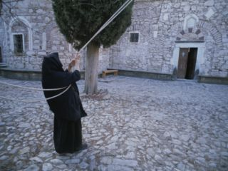 A Nun Pulls on Ropes in a Courtyard at the Nea Moni Monastery Photographic Print by Tino Soriano