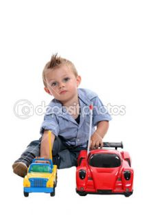 Tot with gelled hair playing with toy cars  Foto Stock